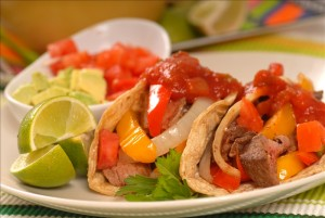 Fajitas with a variety of condiments and limes